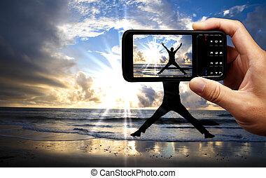 bonito, móvel, telefone câmera, pular, feliz, praia, amanhecer, homem