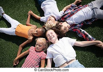 crianças, capim, desfrutando, deitando, dia ensolarado