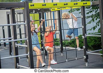 crianças, olhar, excitado, escalando, pátio recreio, ao ar livre
