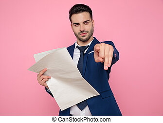 dedo, jornal, homem, atraente, jovem, segurando, apontar