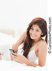 dela, ela, mentiras, enquanto, segurando, sorrir., cama, mulher, smartphone