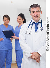 doutor, sorrindo, atrás de, enfermeiras, ele