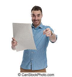 expedir, homem, casual, jornal, segurando, alegre, apontar