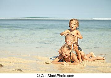 feliz, crianças, praia, três, tocando
