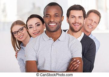 ficar, olhar, mantendo, team., grupo, pessoas negócio, braços, jovem, alegre, confiante, atrás de, câmera, enquanto, africano, cruzado, homem sorridente, ele, fila