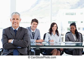 maduras, equipe, seu, gerente, sorrindo, cruzado, atrás de, braços, ele, sentando