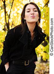 mulher bonita, jovem, amarela, floresta outono, soprando, posar, kiss.