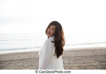 mulher, câmera, asiático, tempo, sorrindo, desfrutando, praia