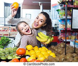 mulher, comprando, pequeno, fruits., menina