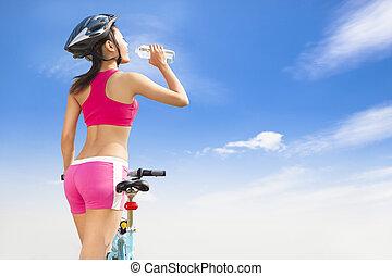 mulher, dobrando, jovem, água, bicicleta, bebendo