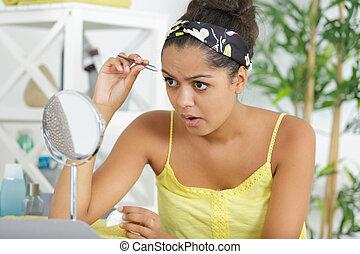 mulher jovem, sobrancelhas, arrancar