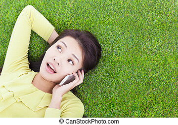 mulher, jovem, telefone pilha, escutar, gramado, sorrindo