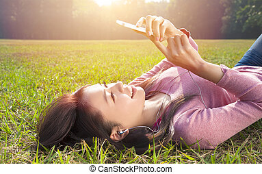 mulher, prado, jovem, telefone pilha, tocar, sorrindo, mentindo