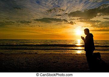 orando, pôr do sol