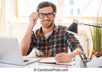 produtivo, work., trabalhando, sentando, ajustar, jovem, escrita, nota, enquanto, seu, lugar, pronto, almofada, sorrindo, eyewear, homem