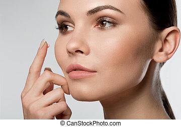 sereno, mulher, aplicando, jovem, rosto, moisturizer