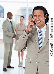 telefone, equipe, seu, falando, sorrindo, executivo, atrás de, ele, jovem