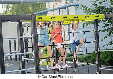 três, olhar, excitado, escalando, crianças, pátio recreio, ao ar livre